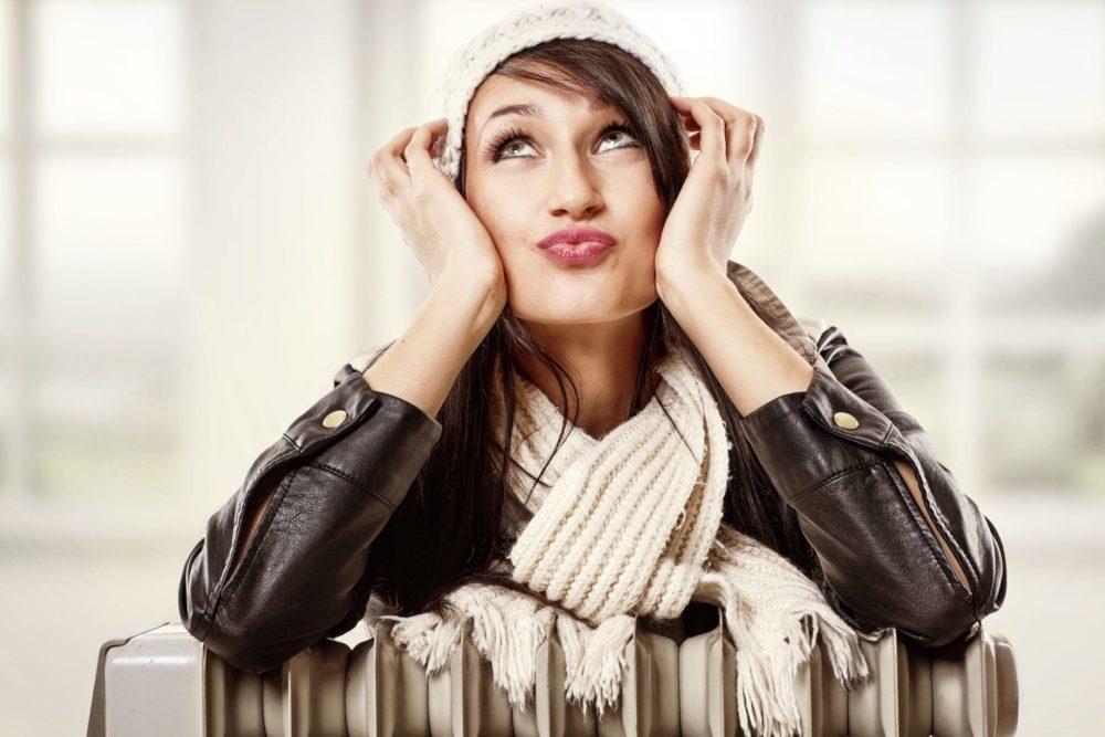 Woman enjoying warmth of radiator